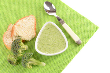 Bowl of broccoli soup on green napkin isolated on white