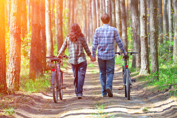 Young happy couple bicycles in the forest and holding hands