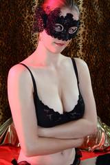 Frau in Dessous trägt Maske