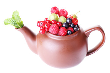 Forest berries and mint leaves in teapot, isolated on white