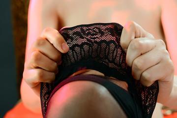 Frau zieht halterlose Strümpfe an