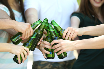 Hands holding beer bottles close up