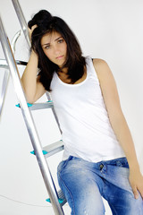 Portrait of beautiful young woman on ladder