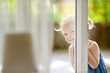 canvas print picture - Cute little toddler girl peeking into a window