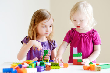 Two little sisters playing with colorful blocks