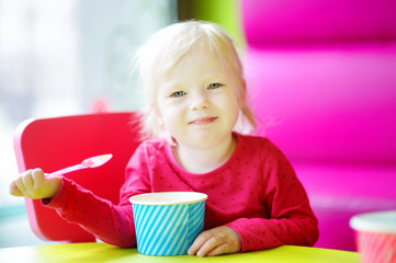 Adorable toddler girl eating ice cream