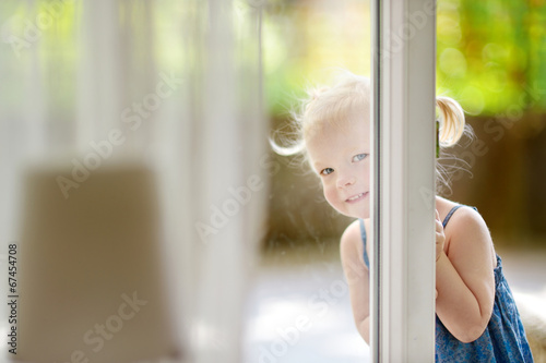 canvas print picture Cute little toddler girl peeking into a window