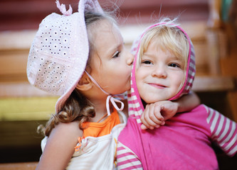 Little girl kisses sister.
