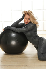 Blonde doing yoga fitness sitting next to ball sport