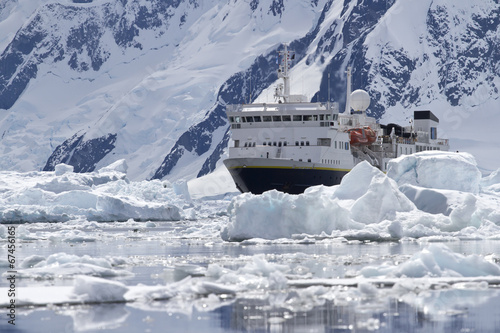 In de dag Antarctica big blue tourist ship in the ice in the background of the Antarc