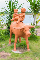 Children on buffalo clay sculpture