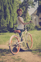 Hipster girl with her vintage bicycle, enjoying beautiful sunny