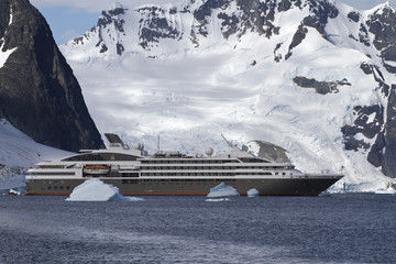 tourist liner sailing among icebergs in Antarctica on a backgrou
