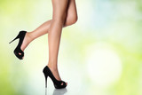 legs with black high-heeled shoes on a sky background
