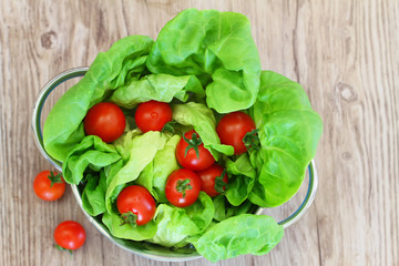 Green lettuce leaves in colander and cherry tomatoes