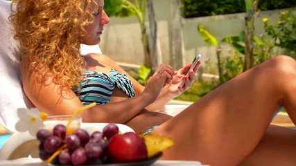 Woman Surfing Internet on Smart Phone at Poolside.