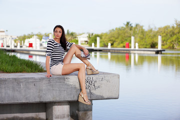 Stock image woman sitting on a ledge by the water