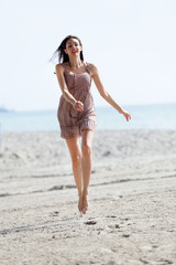 Woman in midair running on the beach