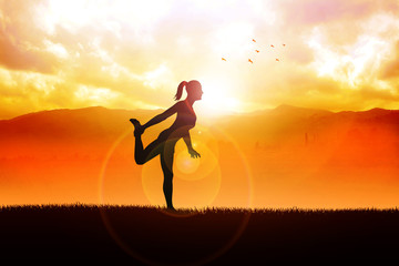 Silhouette of a woman stretching her leg during sunrise