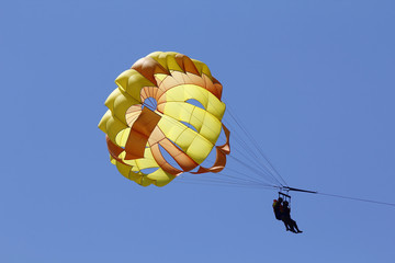 Parasailing against blue sky