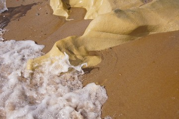 Sandy beach with water foam