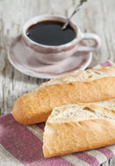 Baguette and cup of coffee on the wooden board