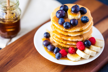 Pancakes with raspberries, blueberries with maple syrup