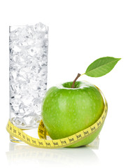 Fresh green apple with yellow measuring tape and glass of water