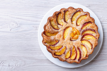 round peach pie on a wooden background top view