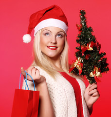 woman with Santa hat holding shopping bags