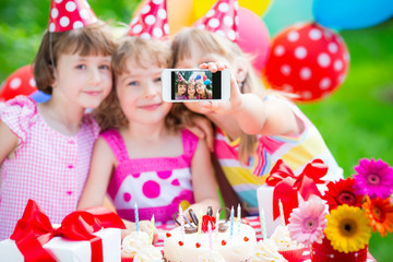 Happy children taking a selfie photo using the smartphone