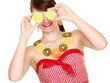 Girl in fruit necklace covering eyes with lemon