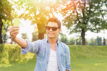 Hipster young mixed race man taking a selfie in park