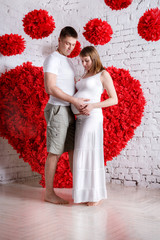 The husband and the pregnant wife on the red heart background