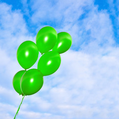 Green balloons on the sky background