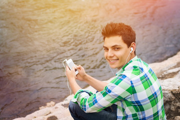 Handsome young man with smartphone sitting by the river