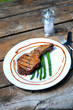 Grilled porkchop with asparagus on a wooden table outdoors