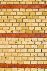 Yellow brickwall with red stripes
