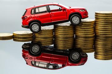 Steigende Autokosten. Auto auf Münzen