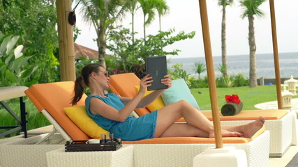 Woman chatting on tablet while lying on sunbed in luxury garden