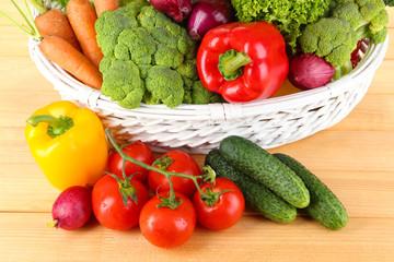 Fresh vegetables in white wicker basket on wooden background