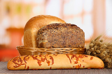 Baked bread in wicker basket on window background