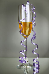 Glass of champagne and streamer after party on gray background
