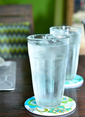 glass of water with ice on wooden table.