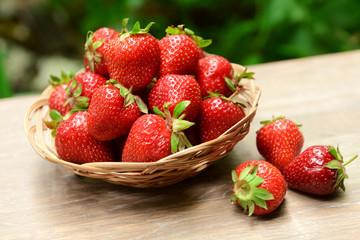Ripe sweet strawberries in wicker basket on table in garden