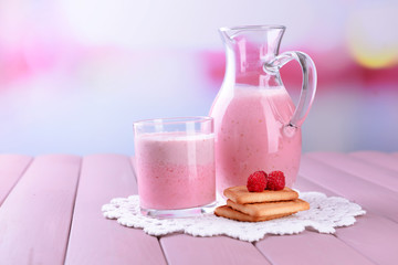 Glass jug of milk cocktail with raspberry taste
