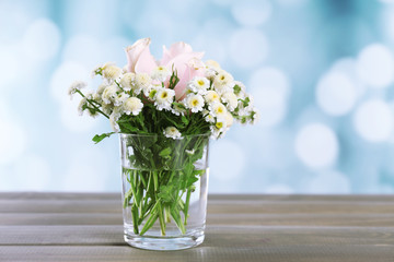 Beautiful flowers on table, on bright background
