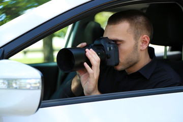 Man in car with photo camera