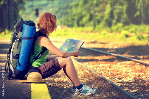 Leinwanddruck Bild Girl wearing backpack and holding map, waiting for a train.
