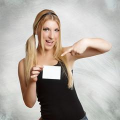 hübsches Mädchen zeigt auf einen Zettel